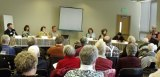 Panelists, left to right: Ryan Dicks, Kimberly Freeman, Tiffany Speir, John Garner, Krystal Kyer, Jacquelyn Whalen and Ryan Mello listen, as LWV's moderator, Lucinda Wingard, (standing) makes the introductions
